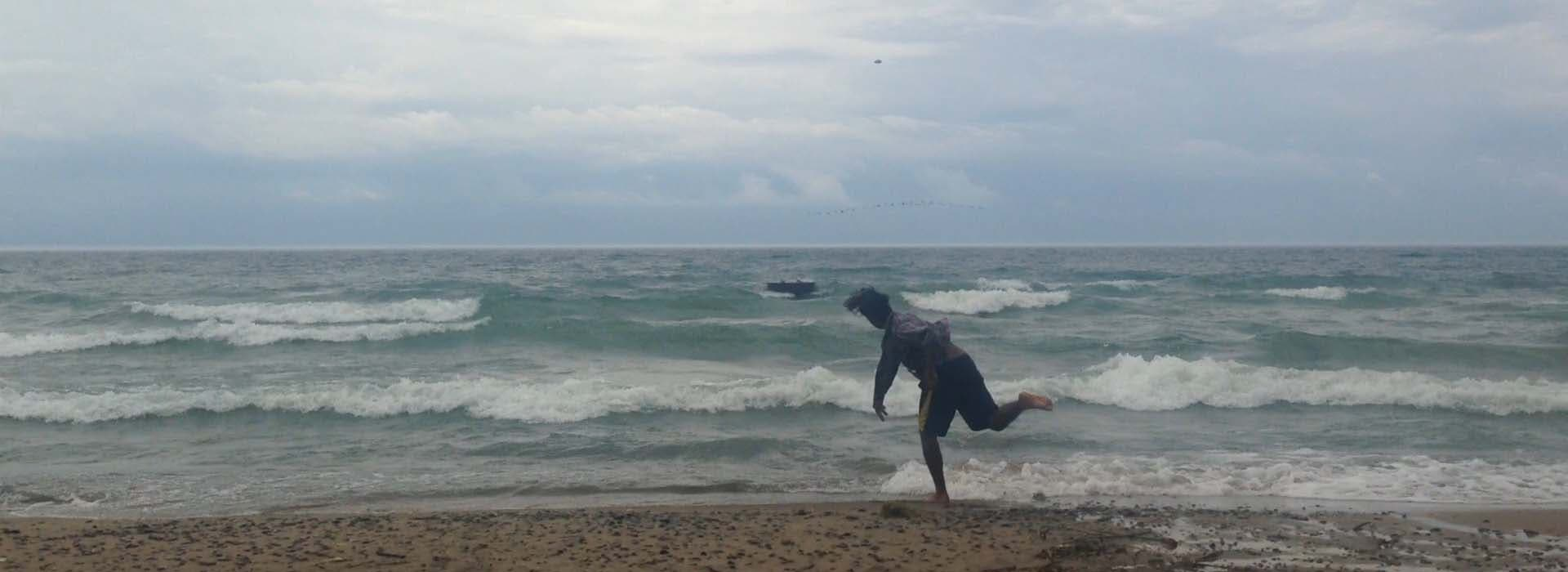 Image of man with ocean in throwing position